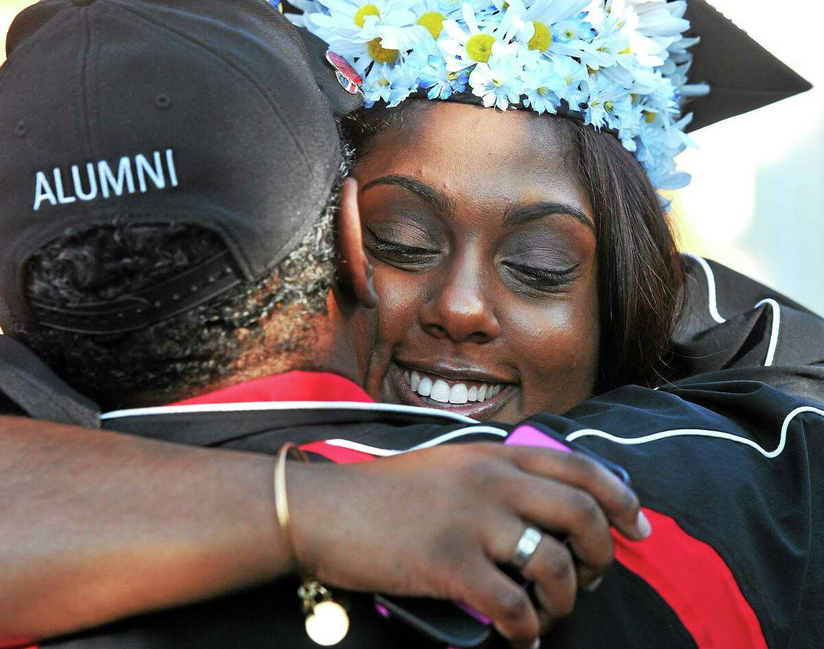 (Peter Casolino-New Haven Register) Graduate, Camille Lavache of Branford, hugs her dad Caminer Lavache, as she gets ready for the 83rd undergraduate commencement exercises at Quinnipiac University. The graduation was delayed and moved due to asecurity threat. 5/18/14 pcasolino@newhavenregister.com