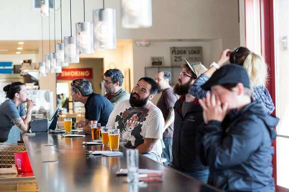 Customers at The Rake, located at Admiral Maltings, sit down at the pub in Alameda, Calif., on Friday, April 27, 2018. Admiral Maltings practices the traditional art of floor malting and turns their malt on the germination floor by hand, which can be seen from the pub that overlooks the malting floor. The Rake carries over twenty beers brewed with their malt in addition to food.