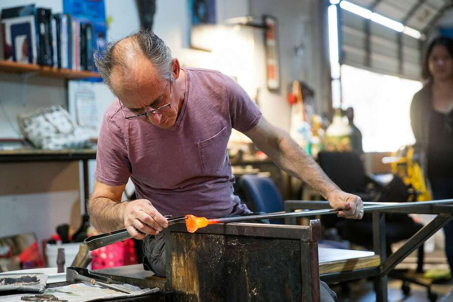 Prax Gore works on making a glass flower while hosting an open studio at Glass Hand Studio during the Second Friday Art Walk in Alameda in April. Photo: Laura Morton
