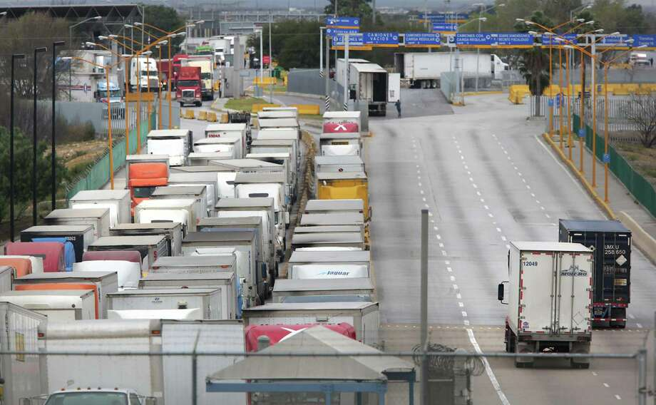 Two trucks, right, leave the U.S. as a long line of trucking traffic waits to enter the U.S. from Mexico at the World Trade Bridge in Laredo, TX, on Friday, Jan. 27, 2017.  This is the traffic in the morning. The traffic is reversed in the evening. Photo: Bob Owen, Staff / San Antonio Express-News / ©2017 San Antonio Express-News