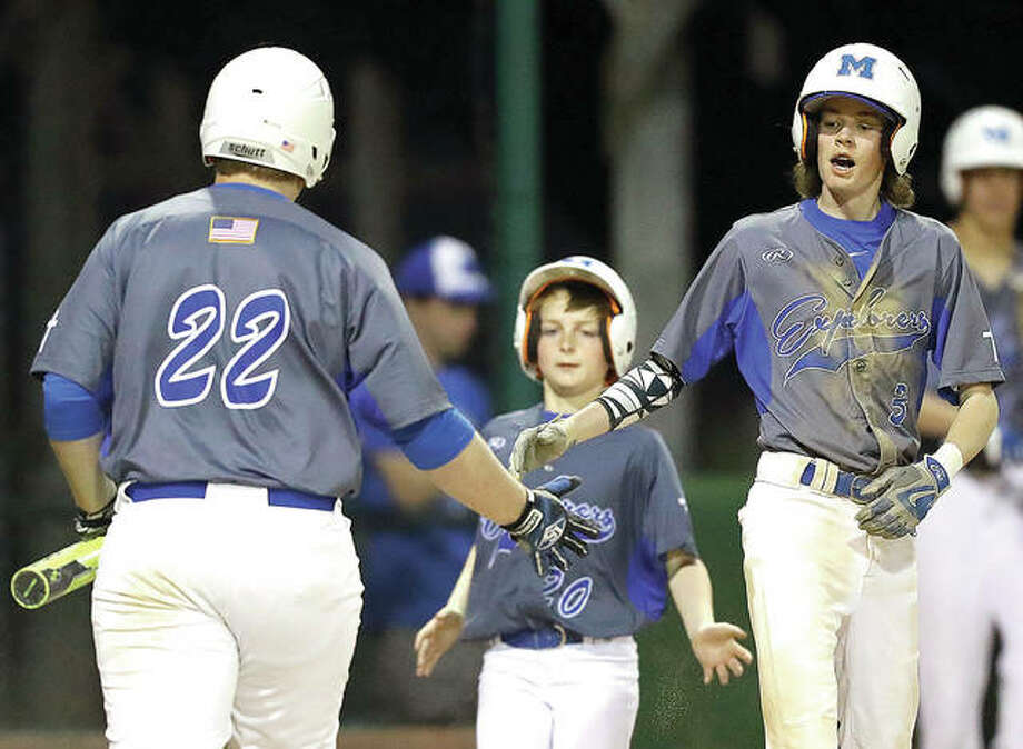 Marquette's Brandon Lloyd (3) and Will Hurst (22) are congratulated by bat boy Will Fahnestock (20) after they scored in Monday night's game against Belleville Althoff at Lloyd Hopkins Field in Gordon Moore Park. The Explorers won 6-0. Photo:     Billy Hurst | For The Telegraph