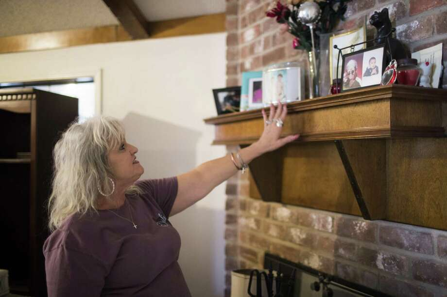 Cherie Cloud extends her hand toward her family photos glad she was able to save them from Hurricane Harvey. Saturday, Feb. 24, 2018, in Houston. ( Marie D. De Jesus / Houston Chronicle ) Photo: Marie D. De Jesus, Houston Chronicle / Houston Chronicle / © 2018 Houston Chronicle