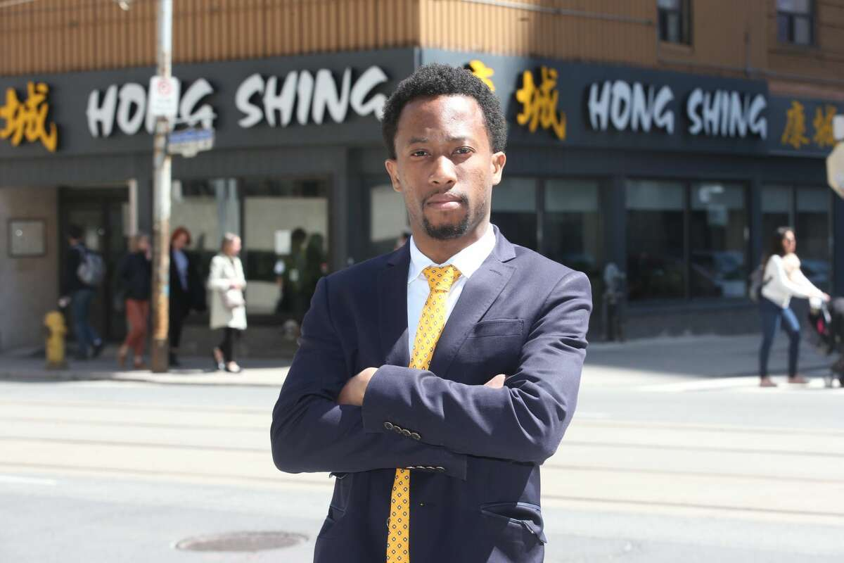 Emile Wickham, who just won a discrimination case with the Ontario Human Rights Tribunal against a restaurant, Hong Shing Chinese restaurant, for violating his human rights in asking him and his friends (all Black) to prepay for their meal poses for pictures in front Ontario Human Rights Tribunal office's.