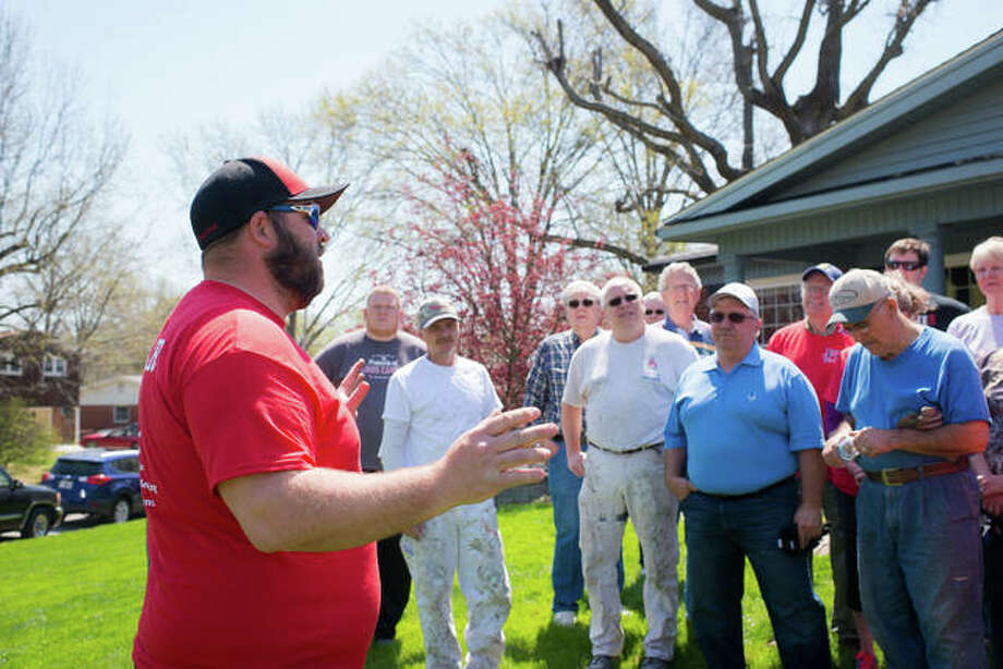 Wiley Heafner, estimator and project manager at Heafner Contracting, who helped coordinate the work day, speaks to volunteers outside the Hanson home Monday. Photo:       Emily Dobson Photography | For The Telegraph