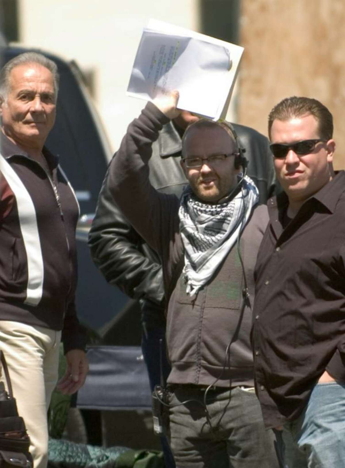 Actor Arthur J. Nascarella, left, and production employees, right, intentionally block a photographers view of Steven Seagal, during a break in filming of Marker, a Steven Seagal film in downtown Stamford, Conn. on Monday, May 7, 2007.