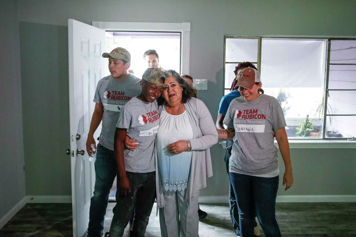 Estela Beaudreault, second from right, hugs Team Rubicon construction site supervisor Teaira Johnson, second from left, as she sees her home, which was flooded during Hurricane Harvey and rebuilt by members of Team Rubicon, for the first time Monday, April 30, 2018 in Houston. Beaudreault's home is the first of 100 homes that Team Rubicon is rebuilding in the Houston area.