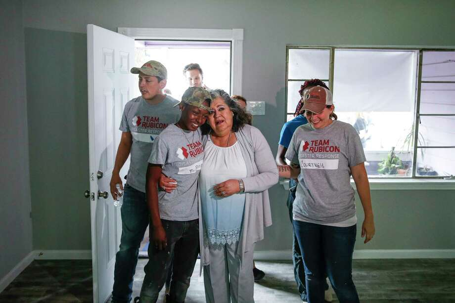 Estela Beaudreault, second from right, hugs Team Rubicon construction site supervisor Teaira Johnson, second from left, as she sees her home, which was flooded during Hurricane Harvey and rebuilt by members of Team Rubicon, for the first time Monday, April 30, 2018 in Houston. Beaudreault's home is the first of 100 homes that Team Rubicon is rebuilding in the Houston area. Photo: Michael Ciaglo, Houston Chronicle / Michael Ciaglo