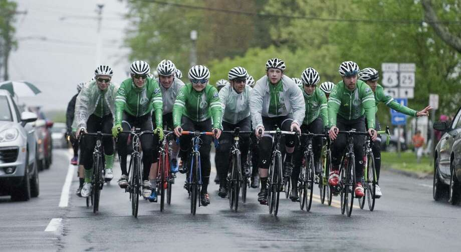 Team 26 cyclists make their way along Main Street in Newtown as they return from last year's 400-mile ride to Washington, DC. Photo: Scott Mullin / For Hearst Connecticut Media / The News-Times Freelance
