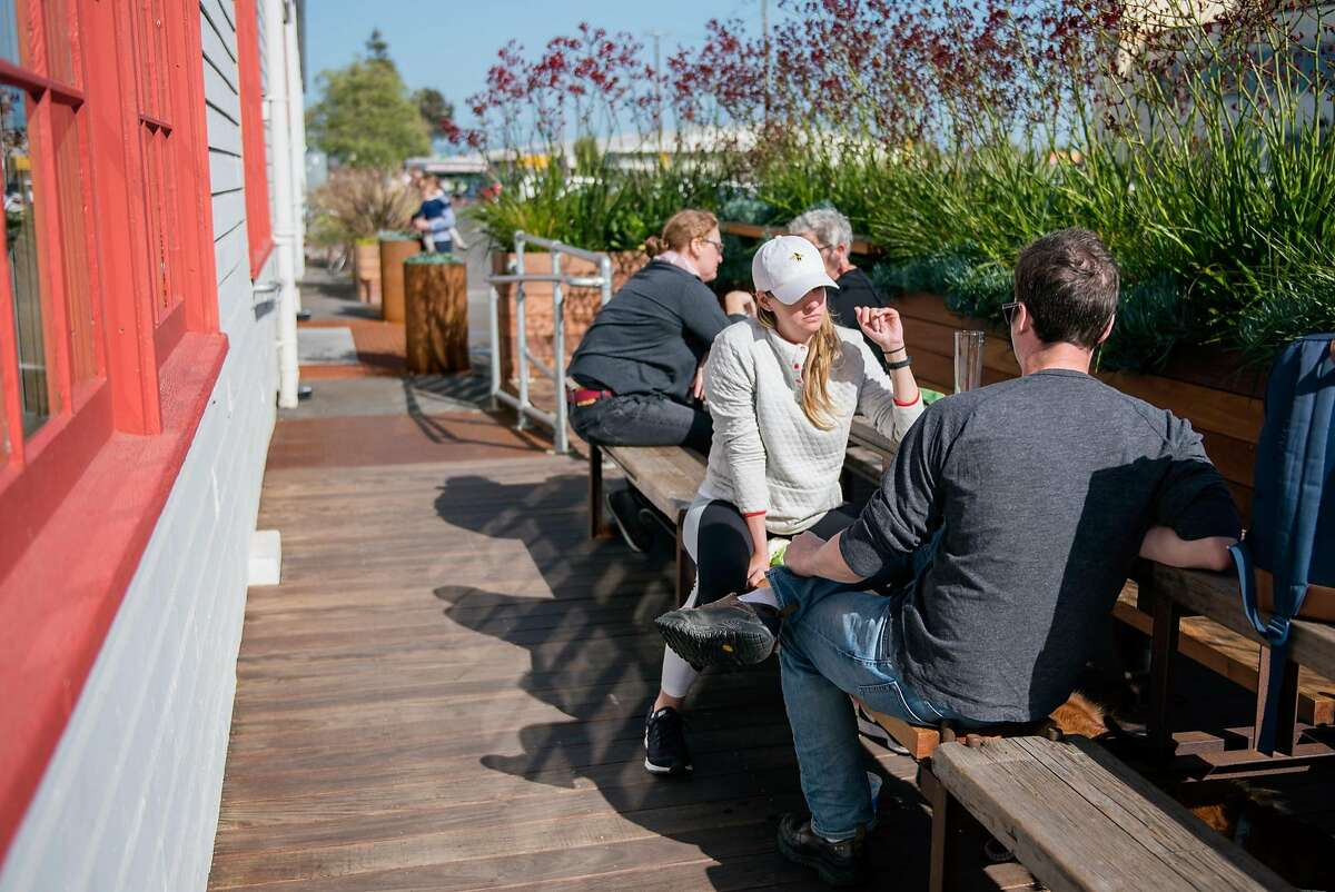 Customers enjoy their beer in the sun outside The Rake, on April 8, 2018.