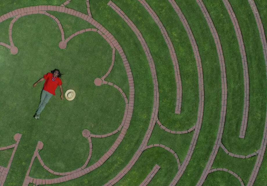 Labyrinth designer Reginald Adams lays in the center of the  labyrinth at the Ruah Center at Villa de Matel, Sunday, April 29, 2018, in Houston. The labyrinth on the site of a former convent of the Sisters of Charity of the Incarnate Word is based on a labyrinth at the Chartres Cathedral in France ( Mark Mulligan / Houston Chronicle ) Photo: Mark Mulligan, Houston Chronicle / Houston Chronicle / © 2018 Houston Chronicle