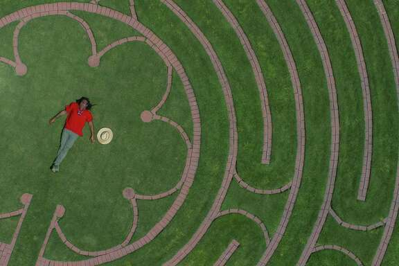 Labyrinth designer Reginald Adams lays in the center of the  labyrinth at the Ruah Center at Villa de Matel, Sunday, April 29, 2018, in Houston. The labyrinth on the site of a former convent of the Sisters of Charity of the Incarnate Word is based on a labyrinth at the Chartres Cathedral in France ( Mark Mulligan / Houston Chronicle )