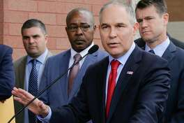 """FILE - In this April 19, 2017, file photo, Environmental Protection Agency Administrator Scott Pruitt speaks at a news conference with Pasquale """"Nino"""" Perrotta, second from left, in East Chicago, Ind. Pruitt is announcing the departure of two top aides amid ethics investigations at the agency. Pruitt says his security chief, Pasquale """"Nino"""" Perrotta, was retiring. He gave no cause, but Pruitt's spending on security at the EPA is the subject of ongoing federal investigations. Pruitt also announced the departure of Albert Kelly, a former Oklahoma banker in charge of the toxic waste cleanups.  (AP Photo/Teresa Crawford, File)"""