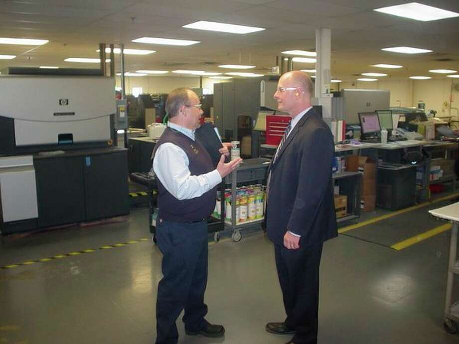Quad/Graphics Plant Manager Harry Iafrate, left, and U.S. Rep. John Moolenaar, R-Midland, discuss production. (John Kennet/jkennett@mdn.net)
