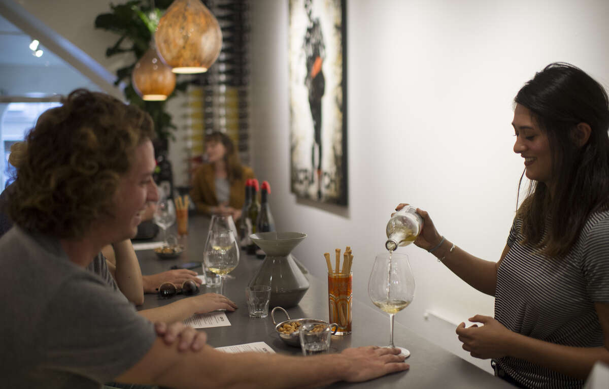 Tasting room associate Amber Provost (right) pours whitewinefor a customer at theScratchWines tasting room in Carmel, Calif. in 2016.
