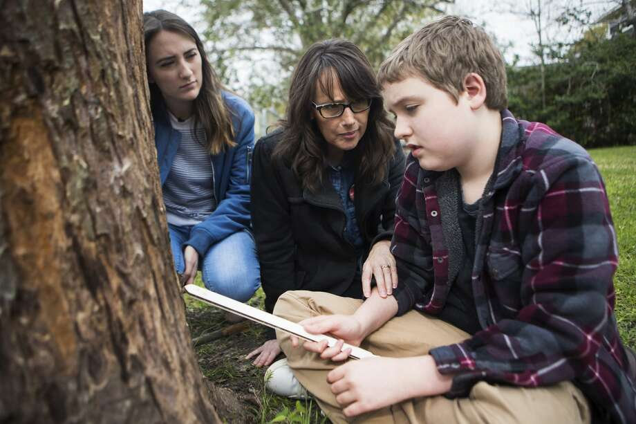 Bonnie Jensen asks her son, Micah, to take a break from obsessively hitting a tree in their front yard. It's a repetitive action he does whenever he's outside. Photo: Marie D. De Jesús
