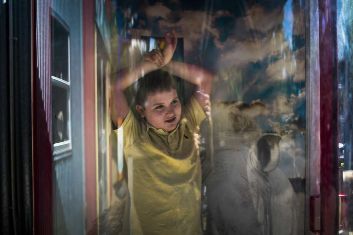 Micah, who has autism and epilepsy, plays in a wind tunnel at the Houston Zoo.