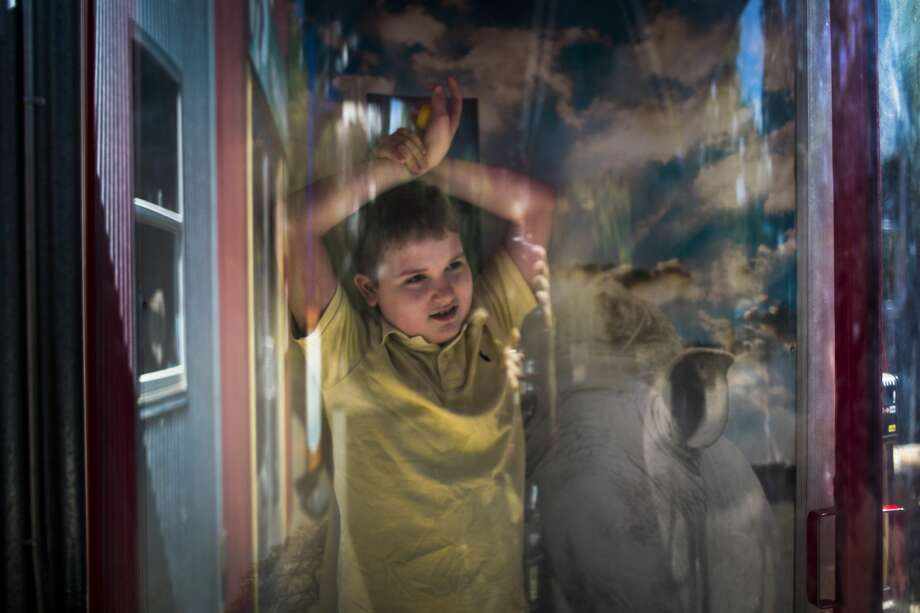 Micah, who has autism and epilepsy, plays in a wind tunnel at the Houston Zoo. Photo: Marie D. De Jesús/Houston Chronicle