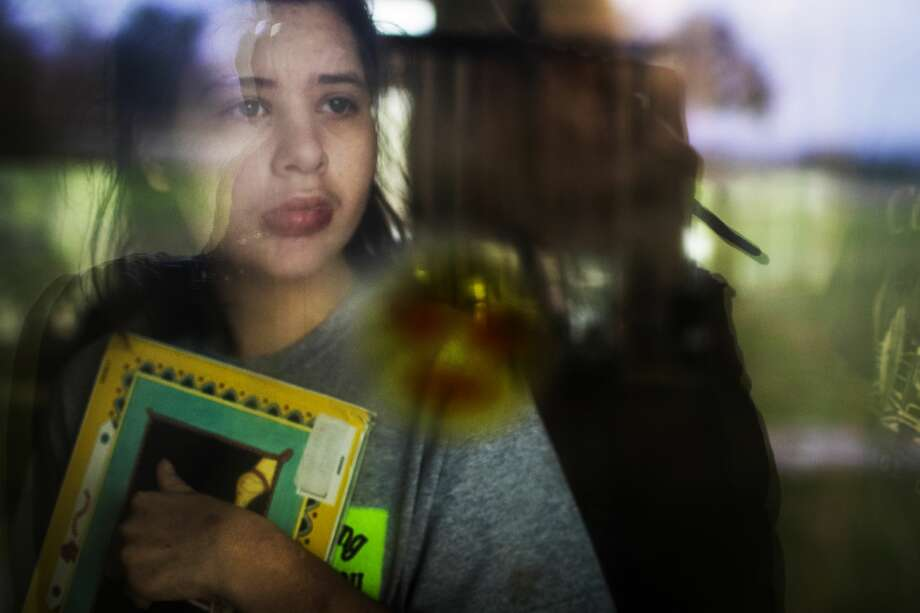 Catherine Carriker, 15, a young book lover, clutches a book to her chest as he looks out the window of her Austin home. Catherine has intractable epilepsy and will be getting medical cannabis in Texas in the summer. Photo: Marie D. De Jesús