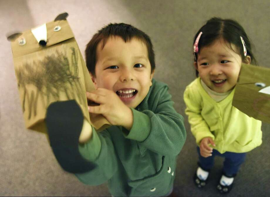 Stamford's Justin Toth, 3, pretends to spray a stinky smell with his paper skunk beside friend Yunha Cho, 2, of White Plains, N.Y., during the Bruce Beginnings program at the Bruce Museum in Greenwich, Conn. Tuesday, May 1, 2018. On Tuesdays in May, children ages 2 1/2 to five are invited to explore the museum's collections and exhibitions through picture books and hands-on activities free of charge with general admission. Themes rotate between art and science, including Smelly Skunks, Lines and Loops, Astronaut, Cosmonaut, Black and White, and Flower Power. Photo: Tyler Sizemore / Hearst Connecticut Media / Greenwich Time