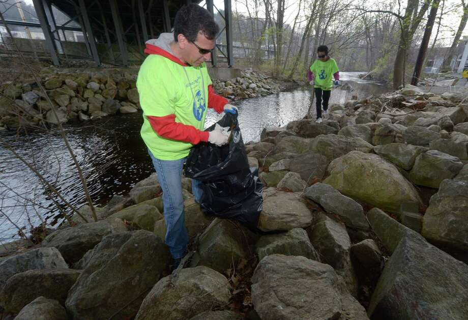 Volunteers and Wilton residents Jason Weisman and Crystal Zhang pick up trash on Saturday, April 28, 2018,  as the Wilton Conservation Commission hosts a town-wide clean-up along the Norwalk River in Wilton, Conn. Photo: Erik Trautmann / Hearst Connecticut Media / Norwalk Hour