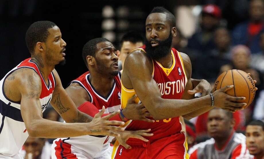 """As a Wizard, Trevor Ariza (left) guarded James Harden in February 2013 before they became Rockets teammates. As to how to stop Harden now, Ariza said """"I don't know, but I'll figure out a way to slow him down."""" Photo: Rob Carr/Getty Images"""