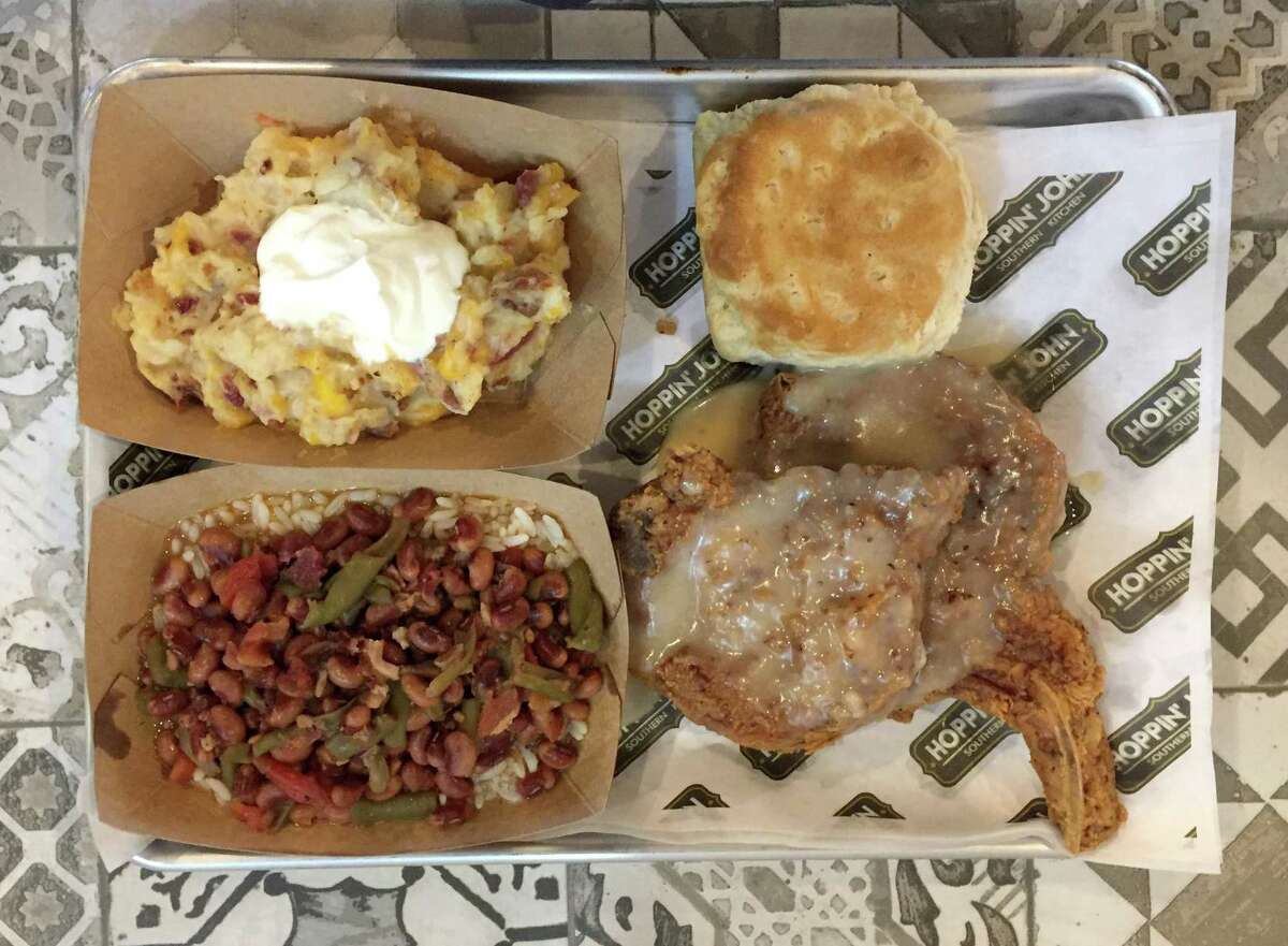 Smothered pork chops with baked potato casserole, stewed black-eyed peas over rice and a biscuit from Hoppin' John.