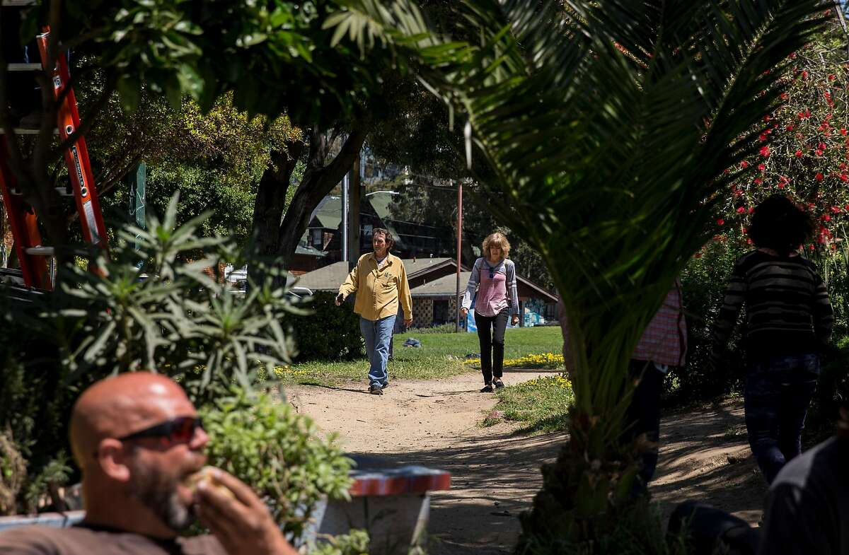 A couple walks down a trail at People's Park in Berkeley, Calif. Tuesday, May 1, 2018