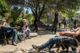 Caleb (left), Matty Bradley (second left), and Ian goodman enjoy the sunny weather while sitting at the edge of People's Park in Berkeley, Calif. Tuesday, May 1, 2018