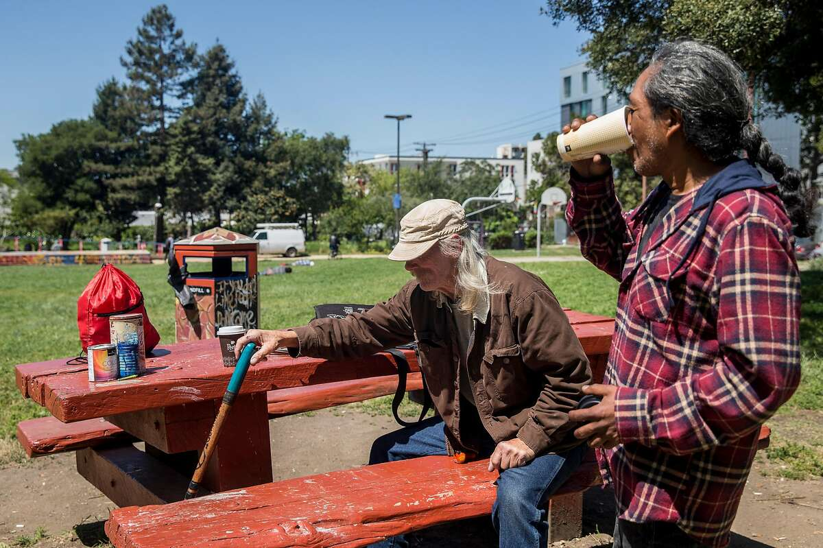 Starkmike, left, and �ero enjoy the sunshine while sitting at a picnic table at People's Park in Berkeley, Calif. Tuesday, May 1, 2018