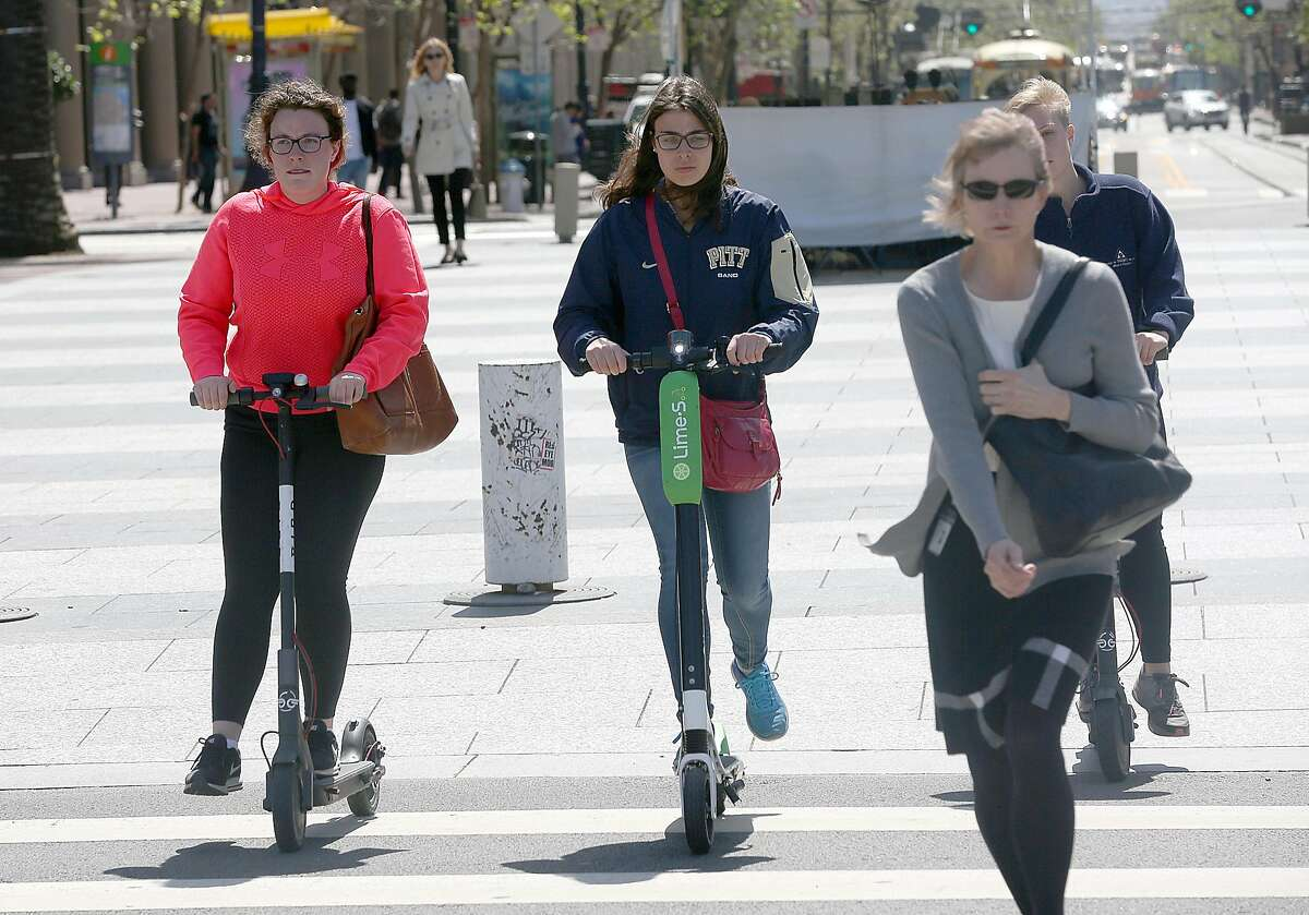 Commuters ride rental scooters on the crosswalk from Market St. to the Ferry building on Monday, April 30, 2018, in San Francisco, Calif.