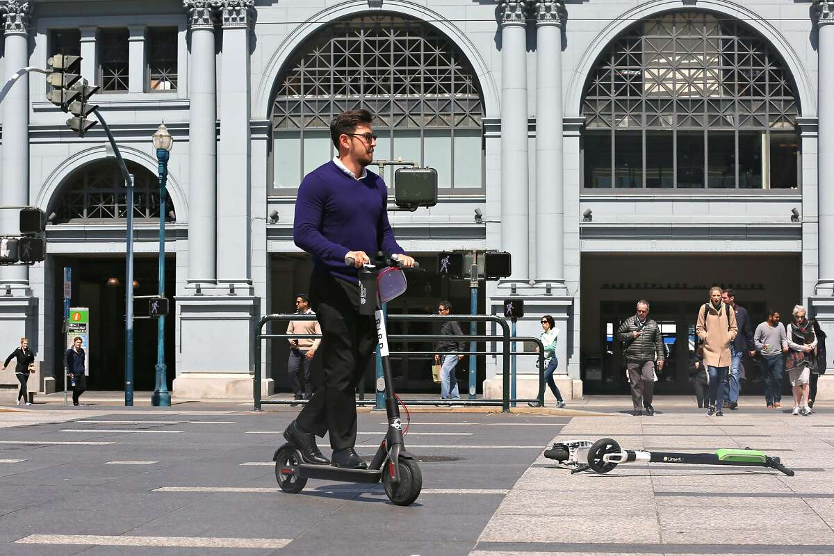 Commuter rides rental scooters at the plaza in front of the Ferry building on Monday, April 30, 2018, in San Francisco, Calif.