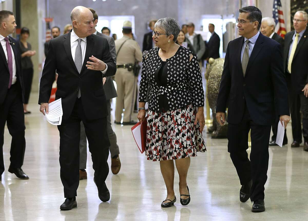 Gov. Jerry Brown, left, talks California Air Resources Board Chair Mary Nichols, and California Attorney General Xavier Becerra as they walk to a news conference to discuss a lawsuit filed by 17 states and the District of Columbia over the Trump administration's plans to scrap vehicle emission standards Tuesday, May 1, 2018, in Sacramento, Calif. The U.S. Environmental Protection Agency has moved to roll back tailpipe emissions standards for vehicles manufactured between 2022 and 2025. (AP Photo/Rich Pedroncelli)