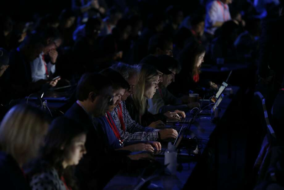 Attendees work on their laptops and other devices as they wait for the Facebook F8 developers conference to begin in San Jose. Photo: Photos By Paul Chinn / The Chronicle