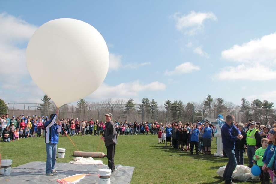 As a crowd of students, teachers and family members watch, Region 10 educators prepare to launch a weather balloon from the Lewis S. Mills High School campus in Burlington on Saturday, April 29. Photo: Photo By Anita Garnett