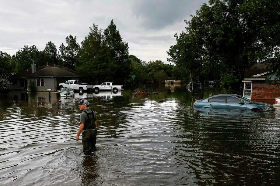 David Hunn walks through Hurricane Harvey floodwaters on Aug. 30 in Pearland's Hickory Creek neighborhood. Local authorities are referring to Harvey's frightening impact to warn residents to prepare for this year's storm season. Photo: Michael Ciaglo, Staff / Houston Chronicle / Michael Ciaglo