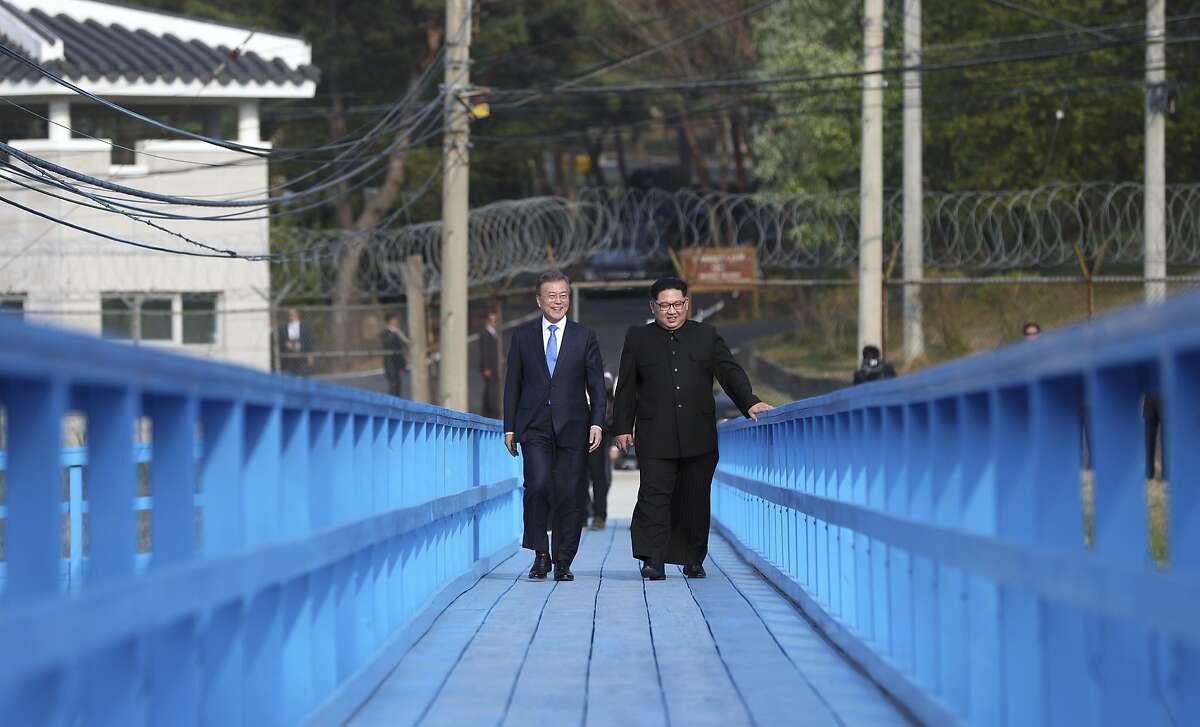 North Korean leader Kim Jong Un, right, and South Korean President Moon Jae-in talk as they walk on the blue bridge at the border village of Panmunjom in the Demilitarized Zone, South Korea, Friday, April 27, 2018. (Korea Summit Press Pool via AP)