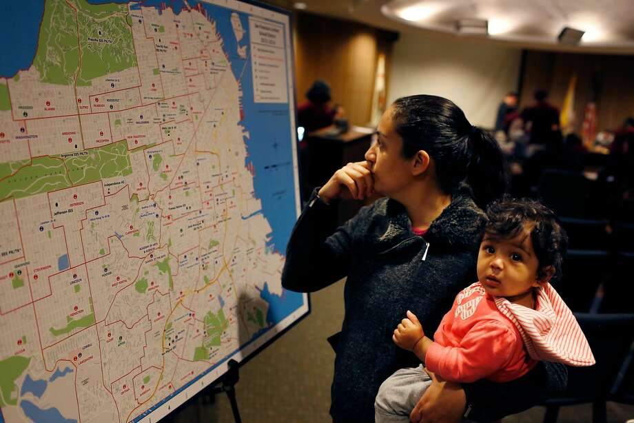 Rabia Mughal holds her seven-month-old daughter, Noor, as she looks over a map of San Francisco Unified School District schools on the last day to hand in Round One applications. Photo: Lea Suzuki / The Chronicle 2015