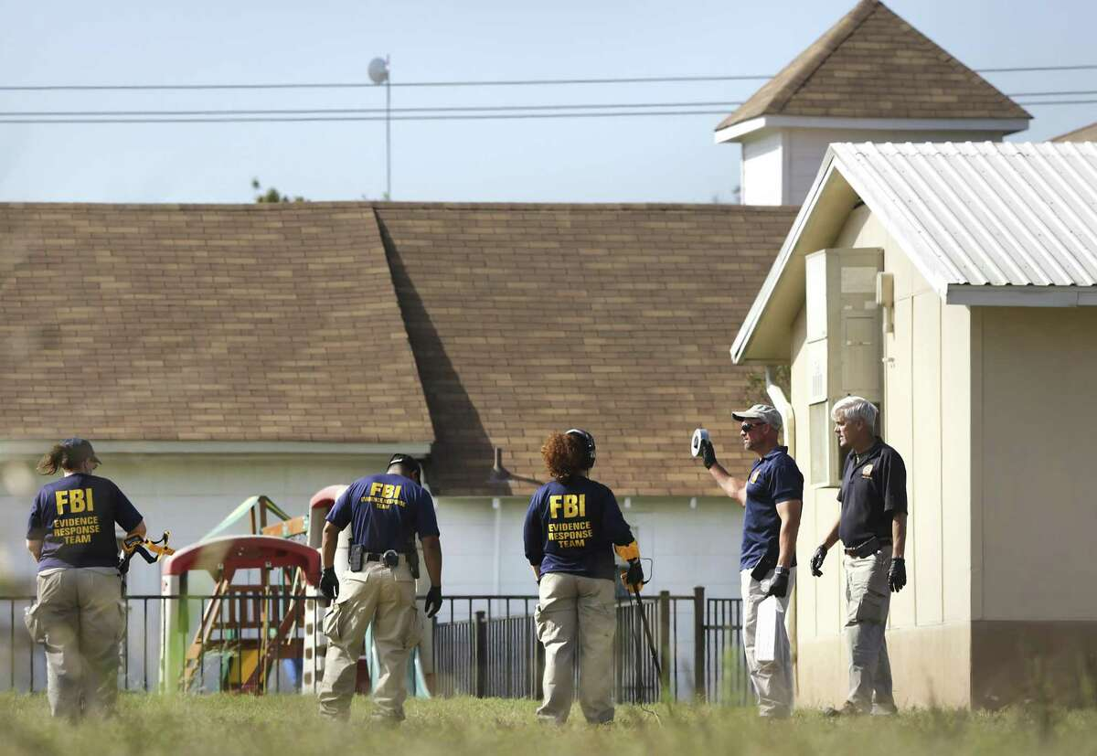 FBI agents use metal detectors as they investigate the area near the scene of the mass shooting at the First Baptist Church in Sutherland Springs, Texas, on Tuesday, Nov. 6, 2017.