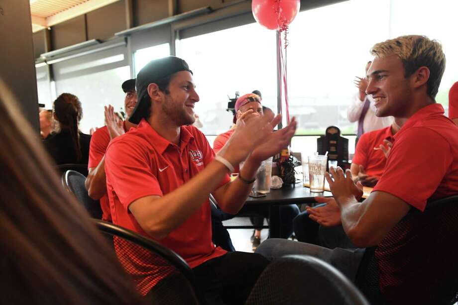 Lamar University men's tennis players Benny Schweizer, left, and Roy Stepanou applaud as the team is announced as Texas A&M's opponent Tuesday during the NCAA tournament watch party at Buffalo Wild Wings on Dowlen Road in Beaumont. (Mike Tobias/The Enterprise)