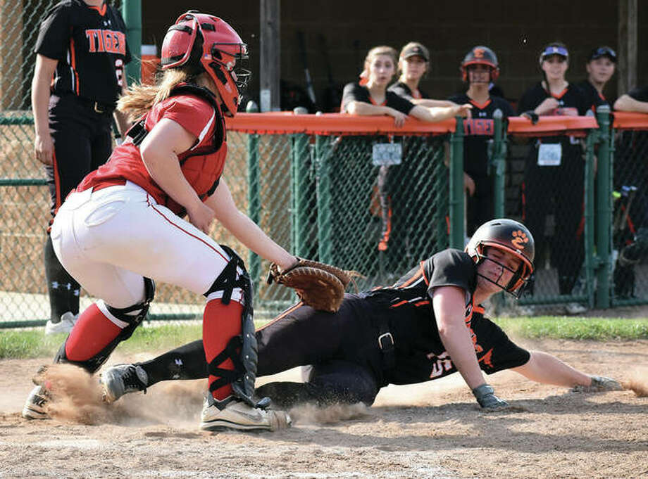 Alton catcher Lynna Fischer (left) tags out Edwardsville's Anna Burke on a play at the plate during a Southwestern Conference softball game Tuesday at the District 7 Sports Complex in Edwardsville. Burke had four hits and three RBIs in the the Tigers' 15-0 win.