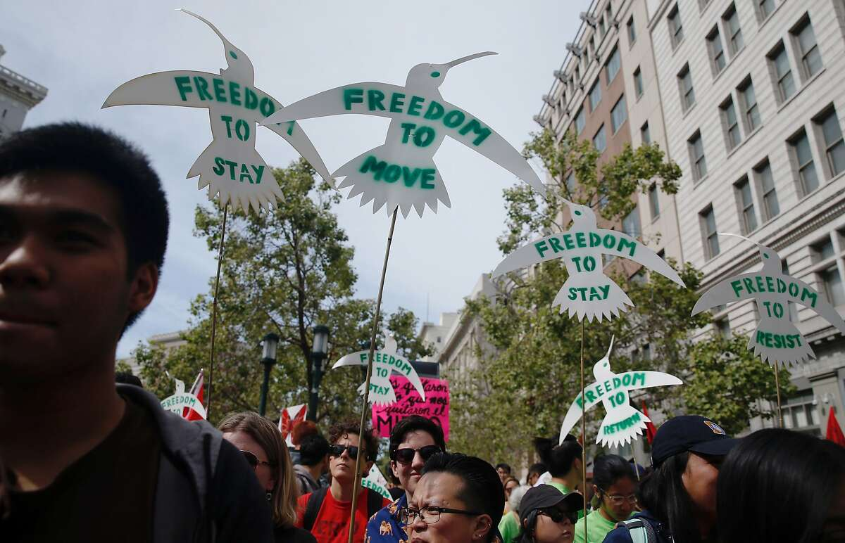 A group of demonstrators carry cut-out birds symbolizing freedom during a May Day rally and march held at Frank H. Ogawa Plaza in Oakland, Calif. Tuesday, May 1, 2018.