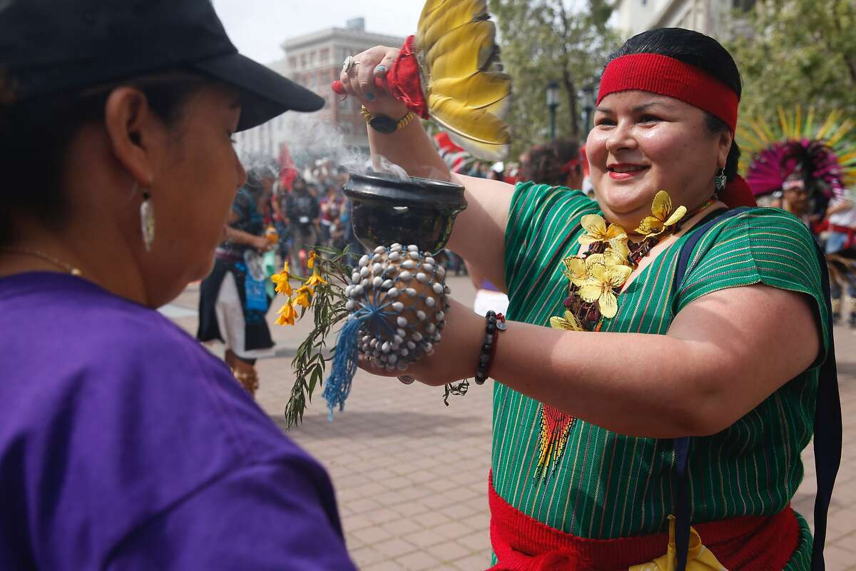 A traditional Aztec dancer blesses members of the group Mujeres Unidas Y Activas attend a May Day rally and march held at Frank H. Ogawa Plaza in Oakland, Calif. Tuesday, May 1, 2018.