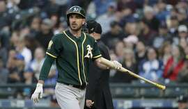 Oakland Athletics' Matt Joyce heads to the dugout after striking out against the Seattle Mariners in the first inning of a baseball game Tuesday, May 1, 2018, in Seattle. (AP Photo/Elaine Thompson)