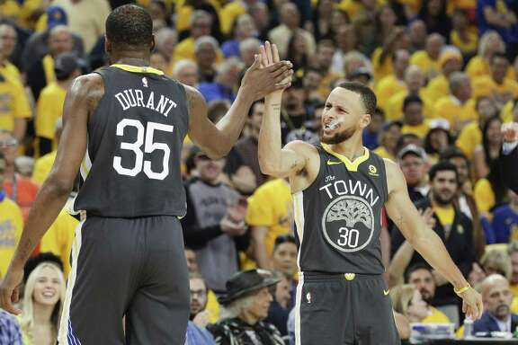 Golden State Warriors' Stephen Curry and Kevin Durant high five in the first quarter during game 2 of the Western Conference Semifinals between the Golden State Warriors and the New Orleans Pelicans at Oracle Arena on Tuesday, May 1, 2018 in Oakland, Calif.