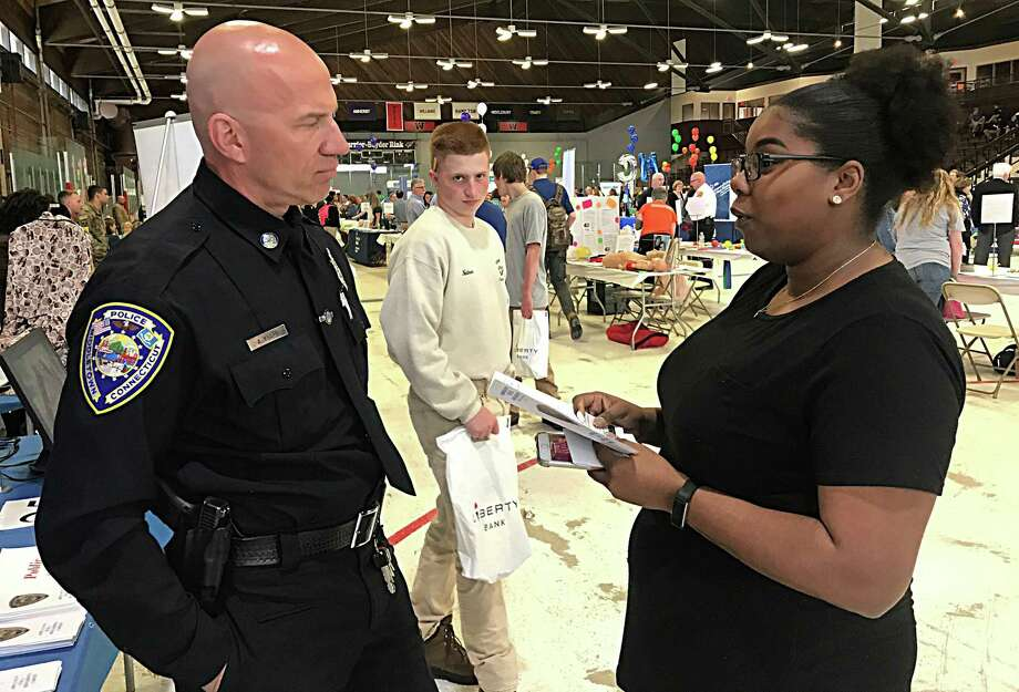 The high school career fair expo at the Wesleyan University Freeman Athletic Center in Middletown Tuesday drew about 1,400 students from area schools. Here, Middletown Police Officer Anthony Knapp speaks to a participant. Photo: Cassandra Day / Hearst Connecticut Media