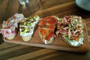 Bruschetta selection at Postino Wine Cafe, from left to right: prosciutto with figs and marscapone; ricotta with dates and pistachios; sweet/tart tomato jam with sheeps cheese; and burrata, bacon, arugula and tomato