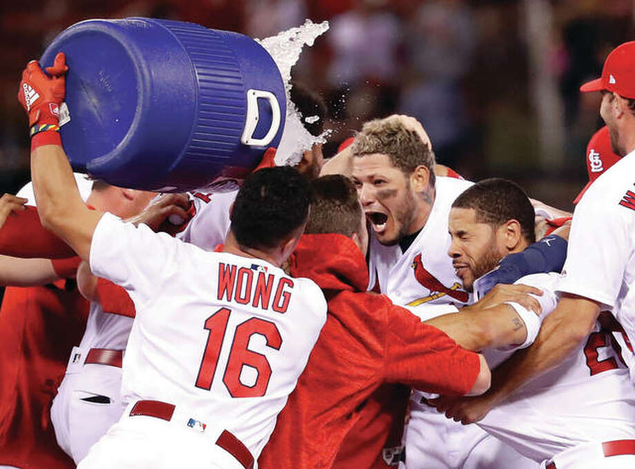 The Cardinals' Yadier Molina, center, is doused by teammate Kolten Wong, left, as Tommy Pham, right, closes his eyes after Molina's walk-off single during the ninth inning against the Chicago White Sox on Tuesday at Busch Stadium. Photo:       AP
