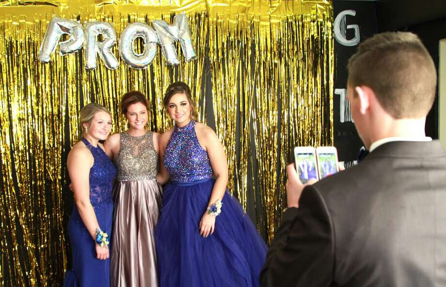 A few attendees take a break from the excitement at Unionville-Sebewaing Area High School's prom on Saturday to snap a picture that will last a lifetime. Photo: Coulter Mitchell/For The Tribune