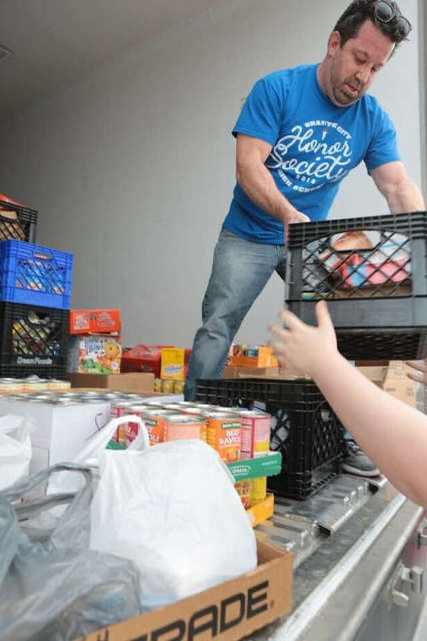 A volunteer helps unload milk crates full of food items collected during the third annual Food for Families Drive. Photo:       For The Telegraph
