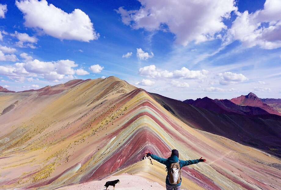 A tourist takes in the mountain's natural wonder at 16,404 feet above sea level in Pitumarca, Peru. Photo: Barcroft Media, Barcroft Media Via Getty Images